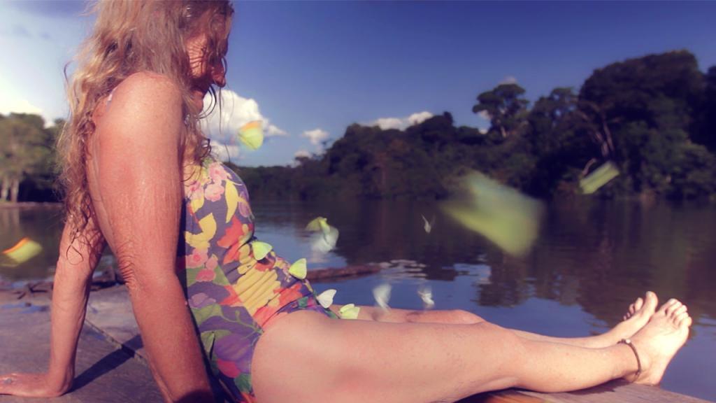 Foto documental Amazona. Una mujer anciana en traje de baño observa el río