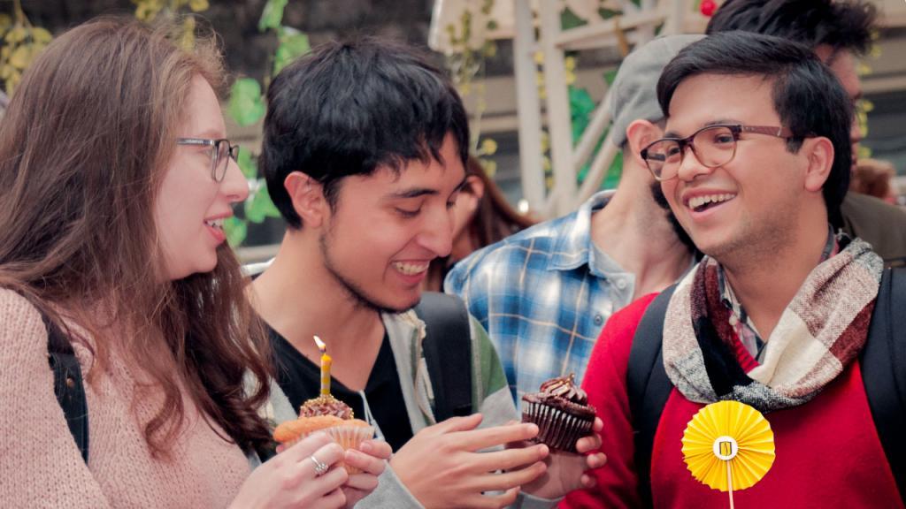 Tres jóvenes con pasteles en la mano