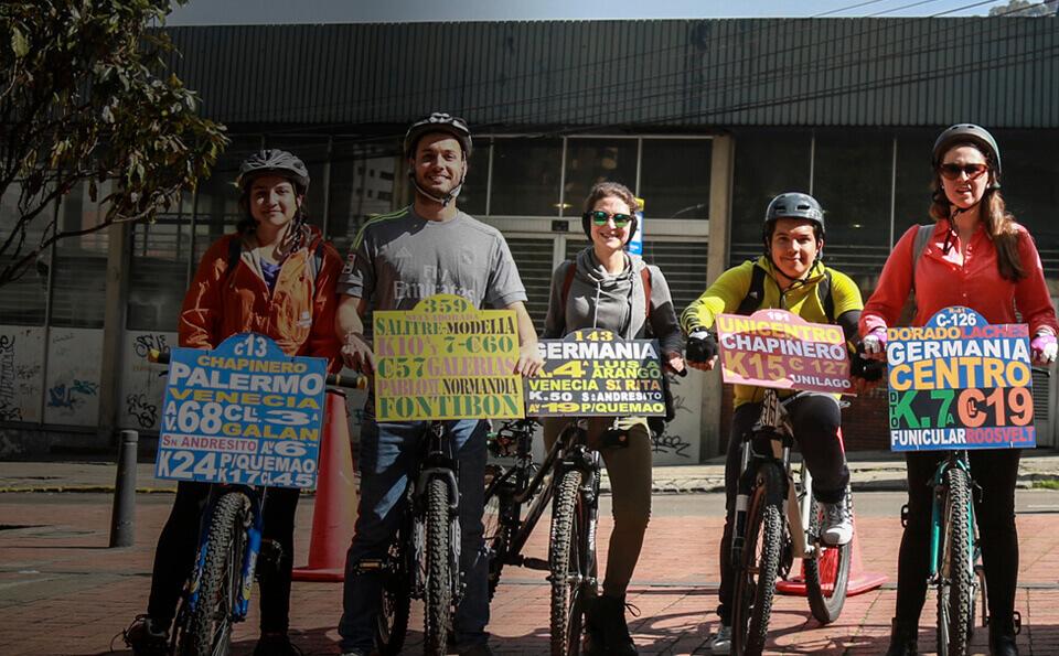 Cinco ciclistas posan frente al biciparqueadero de Uniandes
