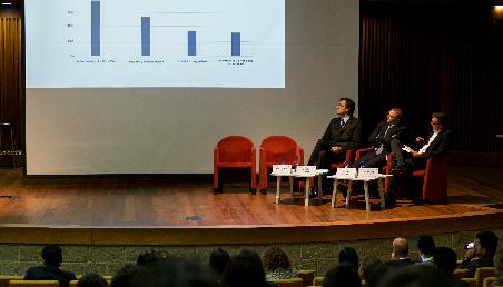 En una tarima, tres panelistas sentados y una pantalla que presenta diapositivas.
