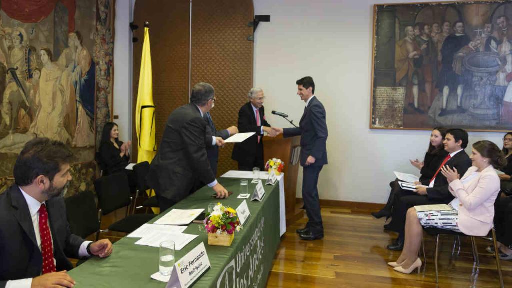 Uno de los becarios recibe el diploma que lo acredita como beneficiario.