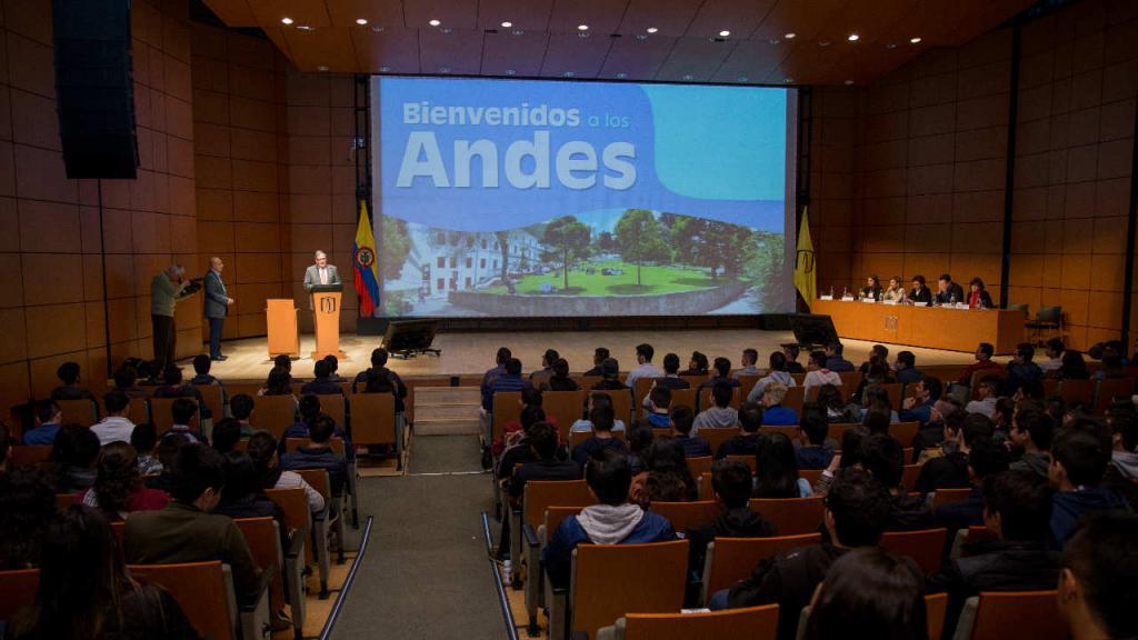 Auditorio lleno de estudiantes viendo una pantalla que dice: Bienvenidos a Los Andes.