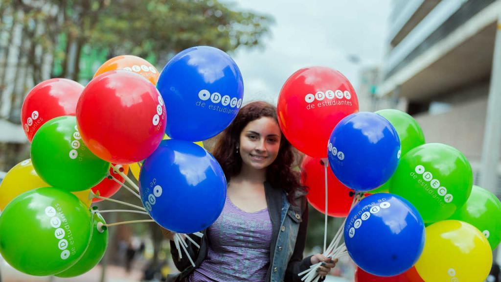 Una señorita con globos de colores inflados en las manos