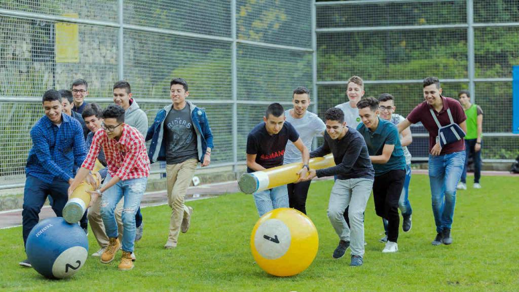 Jóvenes jugando en el cesped con bolas de billar gigantes.