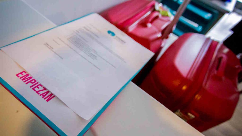 Imagen de un formulario sobre una mesa con el fondo de un equipaje.