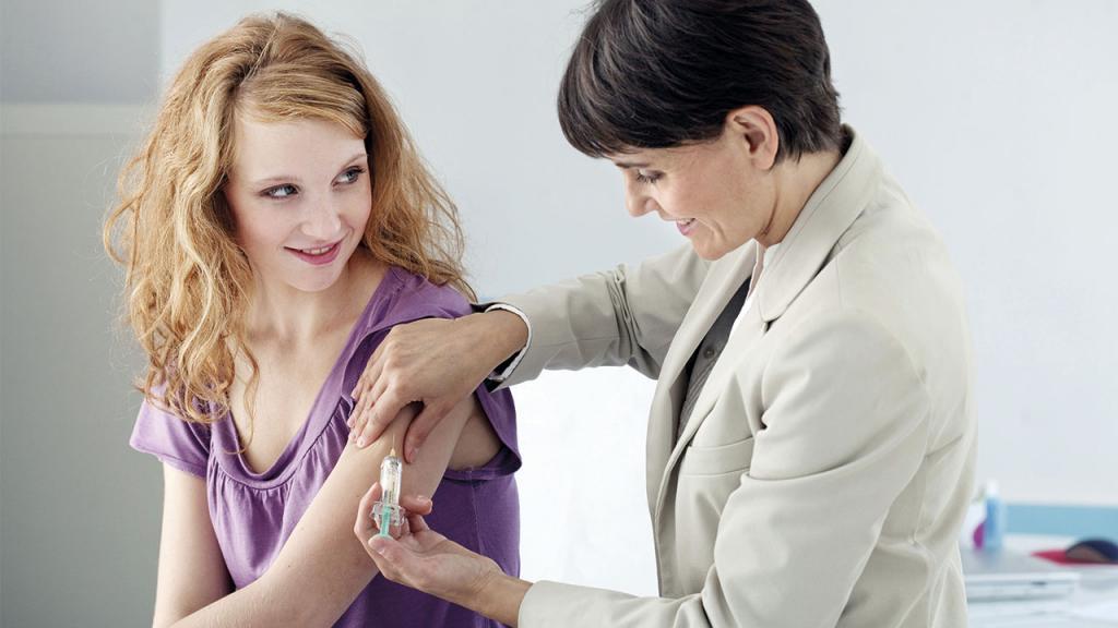 Doctora aplicando una vacuna en el brazo izquierdo de una mujer