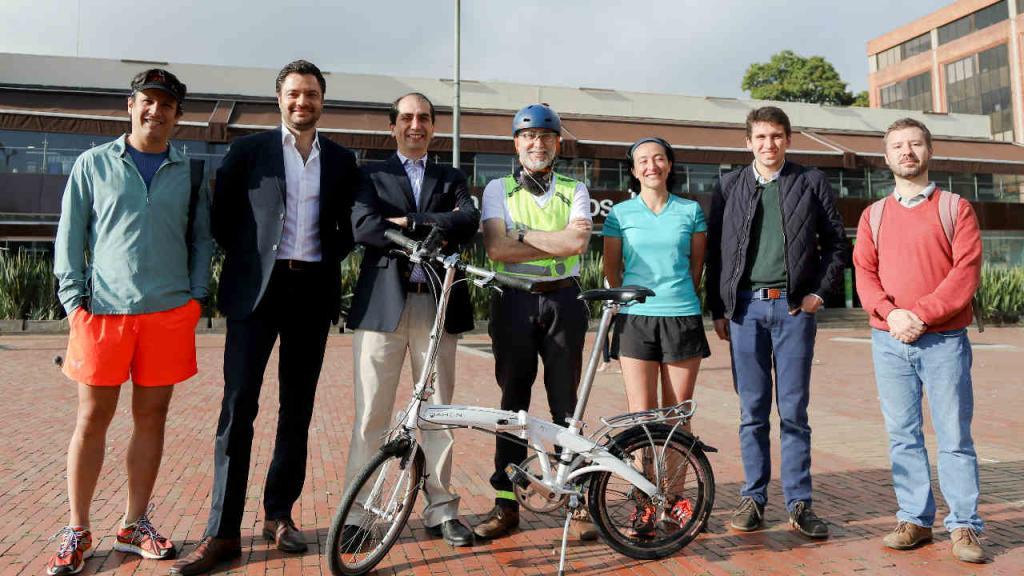 Retrato de siete personas de pie con una bicicleta frente a ellos