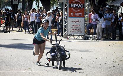 Una persona empuja un vehículo de tres ruedas.