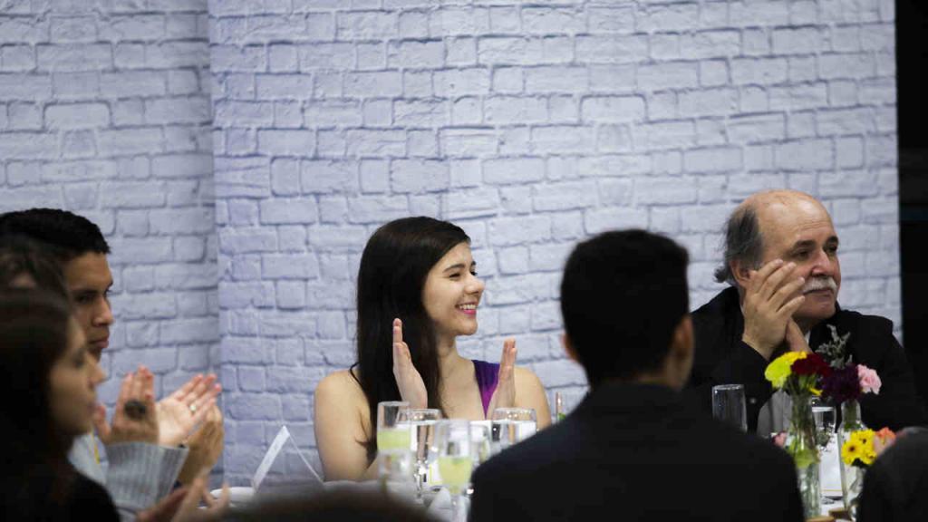 Una estudiante sonríe mientras escucha las intervenciones.