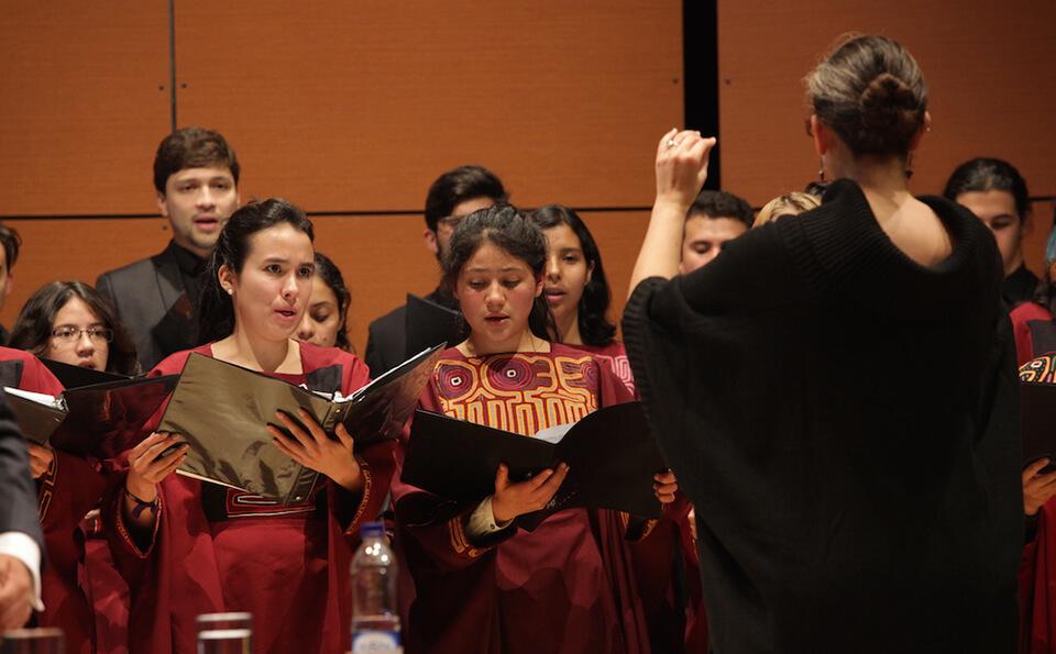 vemos a un mujer vestida de negro dirigiendo un coro en un auditorio