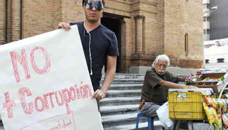 Un hombre que usa un antifaz sostiene un cartel en el que se lee no más corrupción.