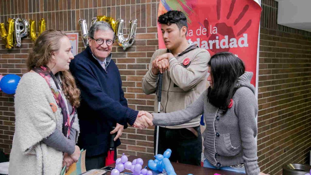 Pablo Navas estrecha la mano de una alumna de la Universidad que fue voluntaria durante la jornada.
