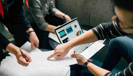 Un grupo de personas discuten al rededor de papeles con apuntes y un computador.