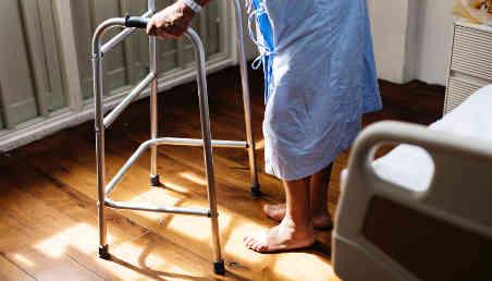 Una persona con discapacidad motora usa un caminador en una clínica.