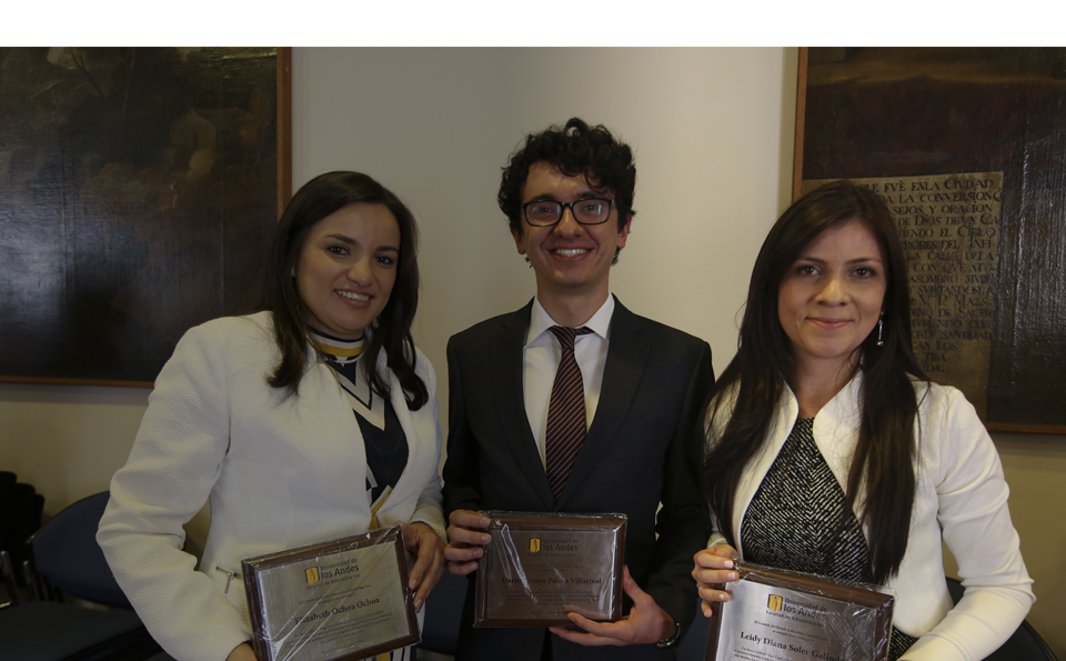 dos mujeres y en medio un hombre, los tres con premio de beca en sus manos.