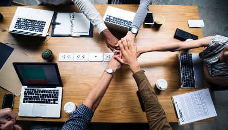 Un grupo de personas entrelazan sus manos sobre una mesa de trabajo.