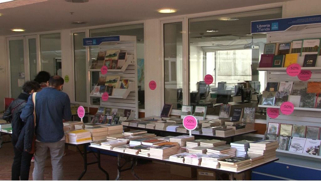 Asistentes a la Feria observan los libros que están exhibidos.