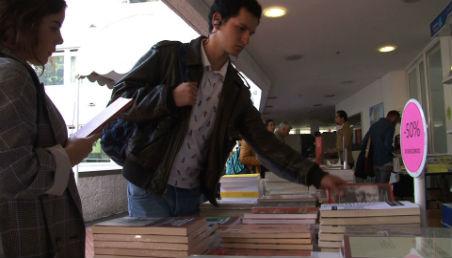 Una persona revisa uno de los libros con 50% de descuento.