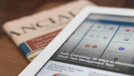 Imagen de un periódico y una tableta con información financiera en ellos.