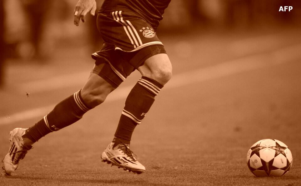 Imagen en sepia con piernas de futbolista en una cancha de fútbol, transportando un balón