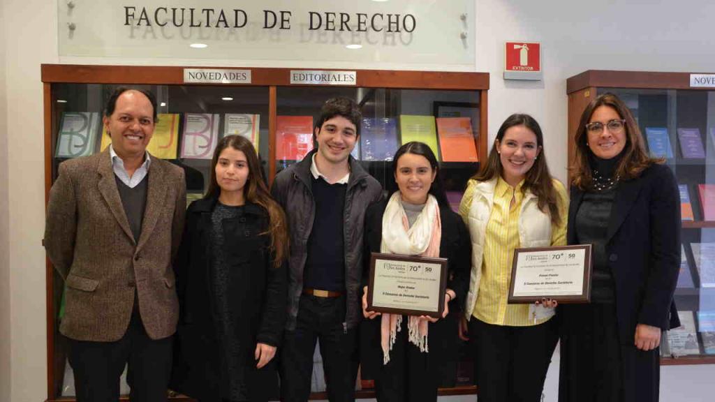 Imagen del grupo ganador, junto a su entrenador y la decana de la Facultad de Derecho.