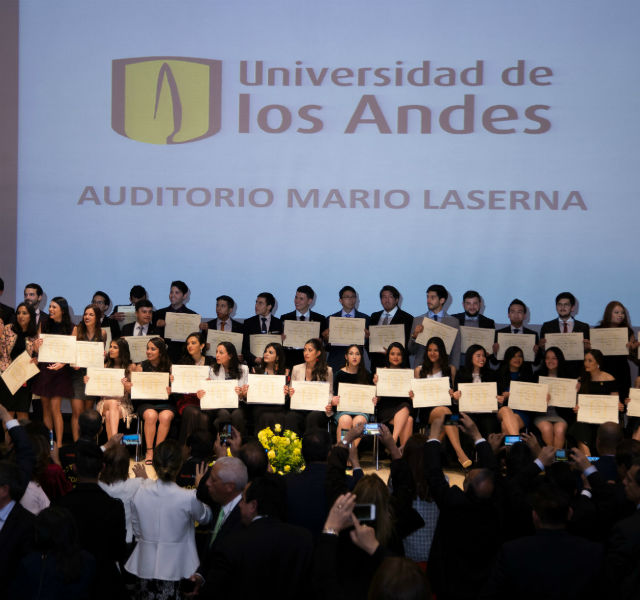 Imagen de todo un grupo de graduandos, sosteniendo su diploma.