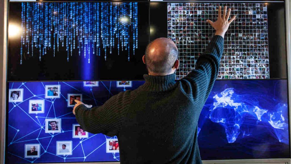 Un hombre manipula una pantalla táctil, demostrando la relación de los humanos con la tecnología.