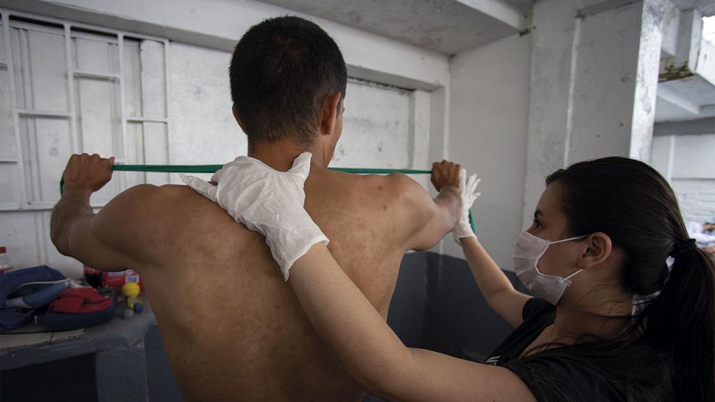 Fisioterapeuta realizando ejercicios con un interno de la cárcel.