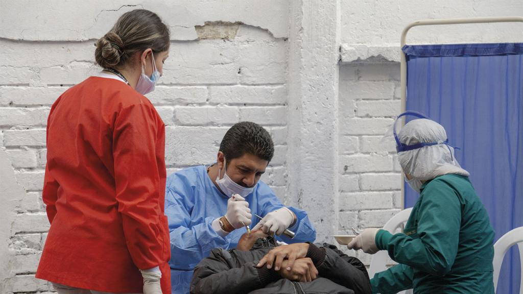 Odontólogo y auxiliares atendiendo a un paciente