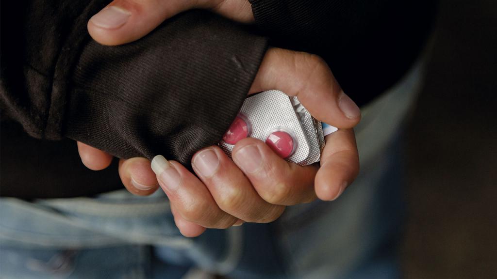 La manos de un interno con tabletas que le dieron para desparasitarse