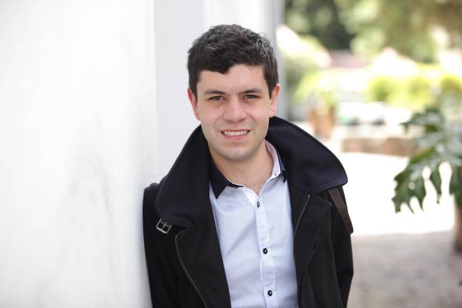 estudiante recostado sobre pared. Usa chaqueta negra y camisa blanca