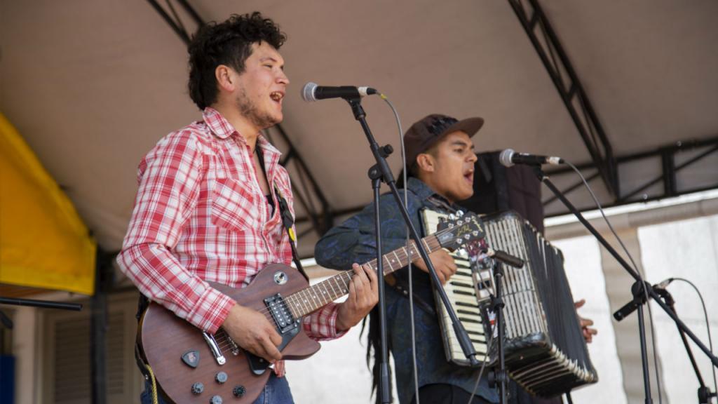 El vocalista tocando la guitarra y a su lado, el acordeonista