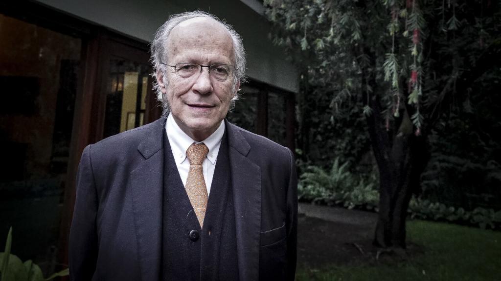Manuel Rodríguez Becerra frente a su casa en el norte de Bogotá. Viste corbata y vestido de paño con chaleco. Un gran panorama verde a su espalda.