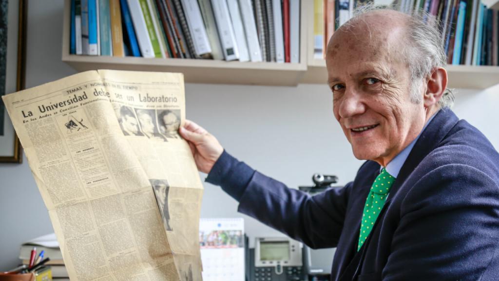Manuel Rodríguez Becerra con un periódico en su oficina en la Facultad de Administración de la Universidad de los Andes.