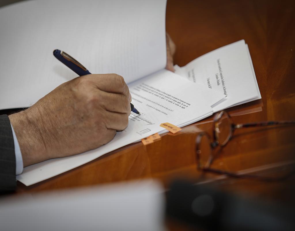 Una mano firma un documento