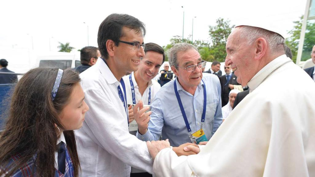 El papa Francisco le da la mano al profesor Enrique Chaux de Los Andes, junto a una niña de Aulas en Paz.