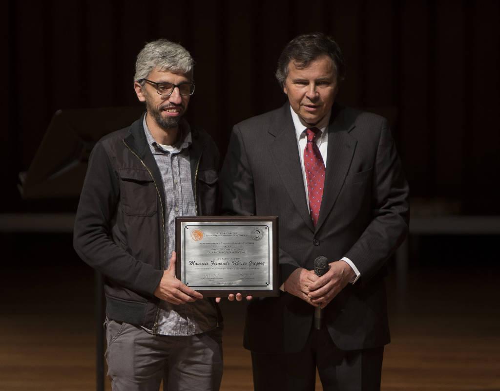 El profesor Mauricio Velasco recibe una placa con el reconocimiento por su trabajo investigativo.