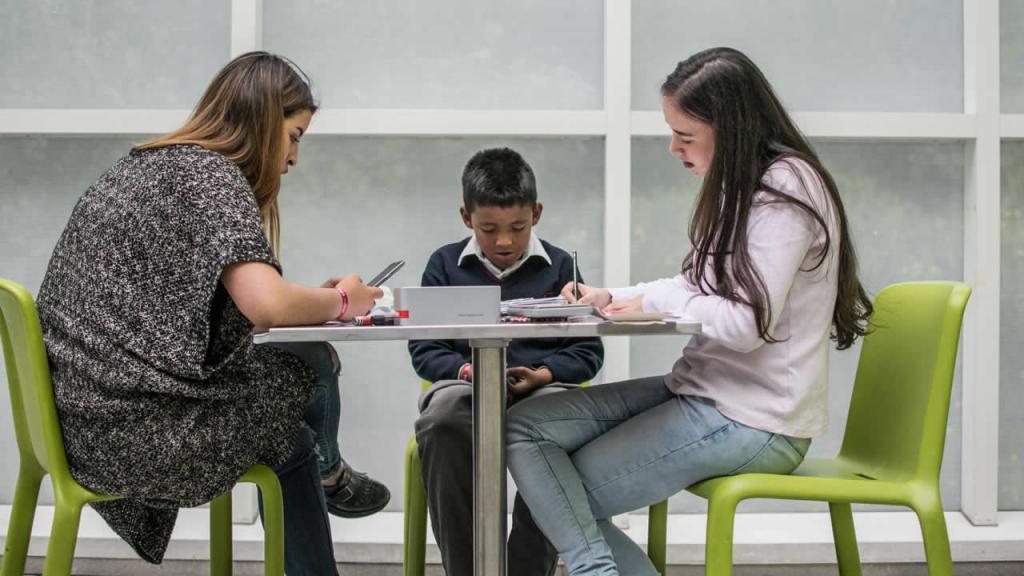 Mujeres y niño escriben en una mesa