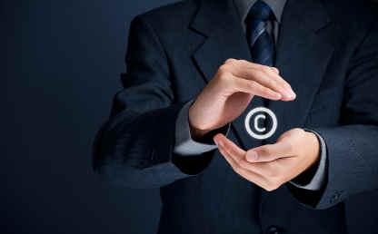 Un hombre sostiene el símbolo de la propiedad intelectual.