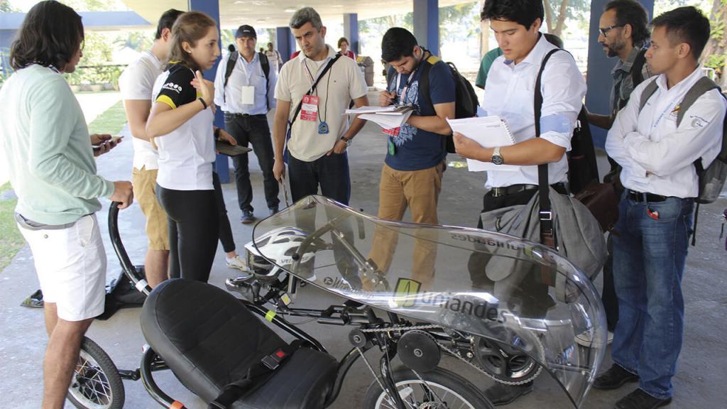 Seis personas rodean un vehículo de tres ruedas