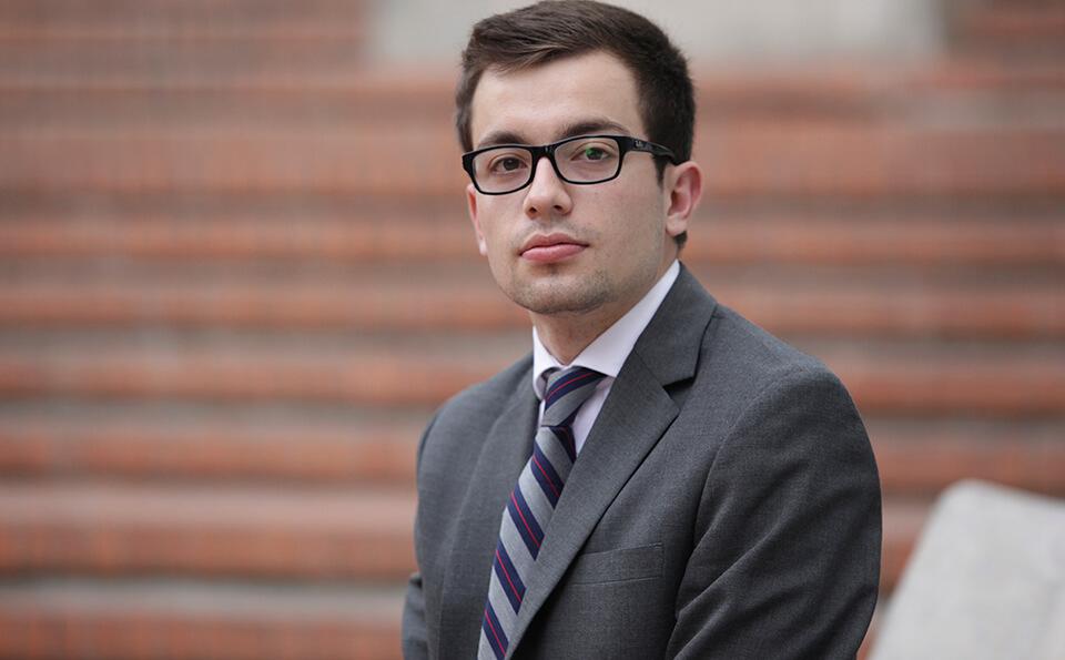 Estudiante graduando con saco y corbata, lo vemos sentado y al fondo se ven unas escaleras