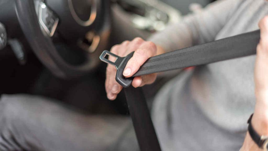 Un hombre a punto de cerrar su cinturón de seguridad en un auto.