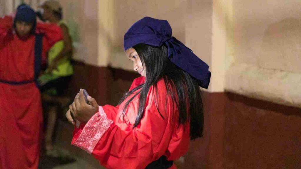 Una feligrés se toma una foto con un celular.