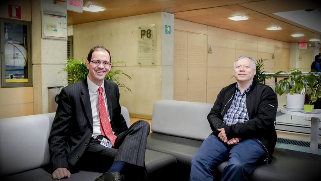 Dos hombres conversan sentados en un sofá