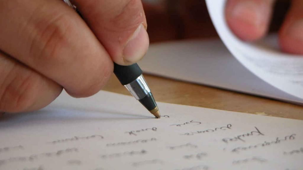 Una persona escribe sobre una hoja de papel.