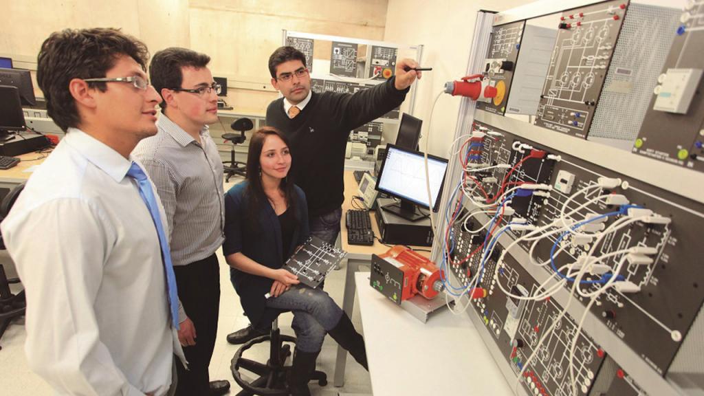 Tres estudiantes y un profesor en un laboratorio de electrónica