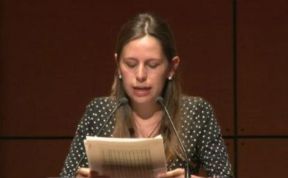 mujer leyendo unas hojas en un auditorio