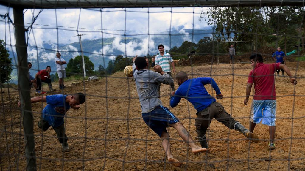 Hombres jugando fútbol. La escena se ve a través de la red de una cancha.