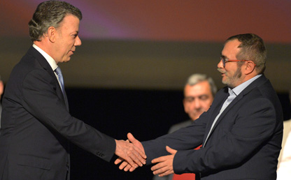 El Presidente de Colombia, Juan Manuel Santos y el jefe de las Farc, Rodrigo Londoño, alias 'Timochenko', se saludan luego de firmar el acuerdo de paz.