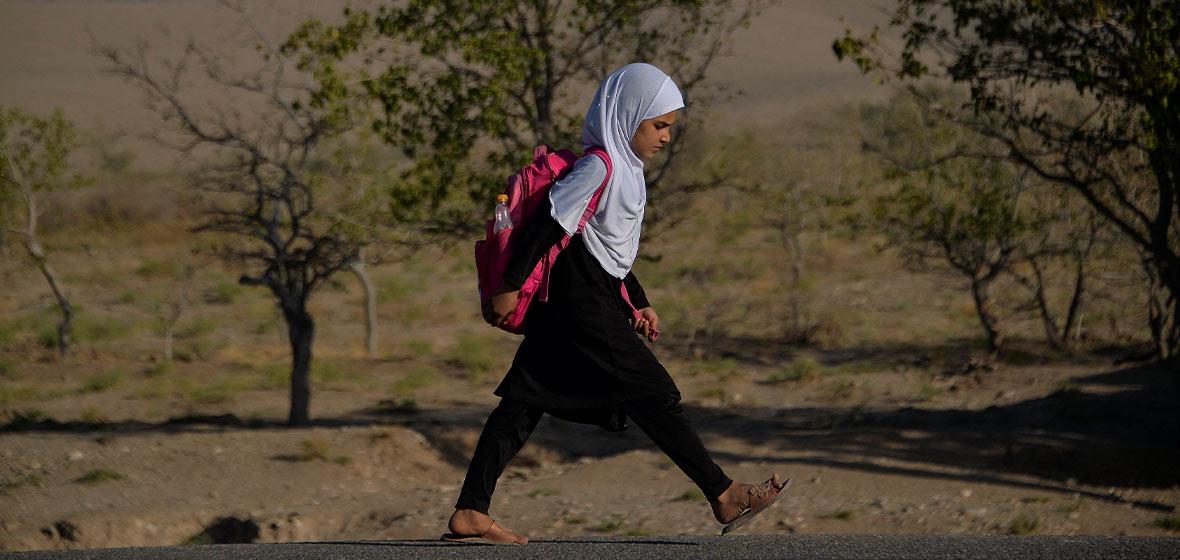 Niña afgana camina con una maleta en sus hombros.